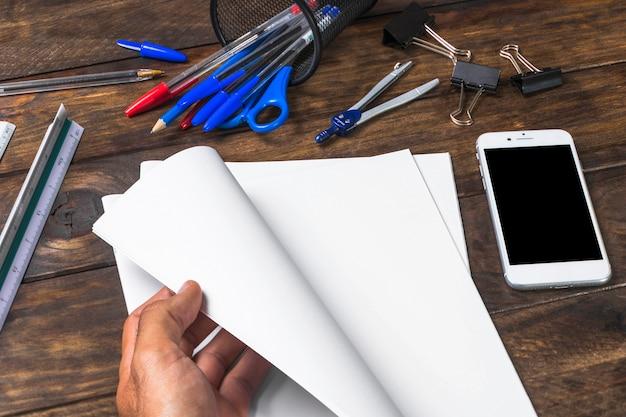 Nahaufnahme einer drehenden seite der person mit schreibwarenämtern und mobile auf tabelle