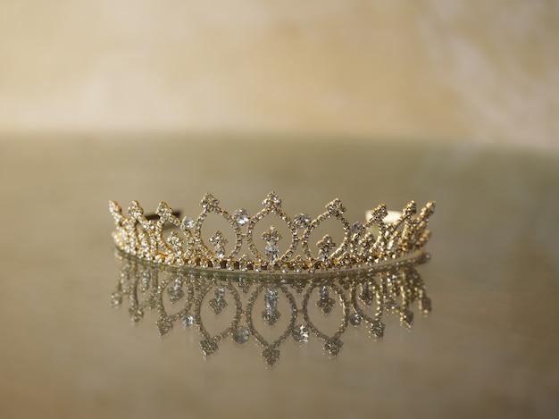 Nahaufnahme einer eleganten krone, die auf der glasoberfläche unten reflektiert wird