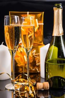 Nahaufnahme einer entkorkten flasche champagner mit zwei gefüllten gläsern im stillleben mit goldenen weihnachtsgeschenken, weißen kerzen und gekräuseltem band
