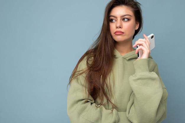 Nahaufnahme einer ernsthaft verärgerten attraktiven jungen frau, die einen stylischen hoodie trägt, der mit dem handy hält?