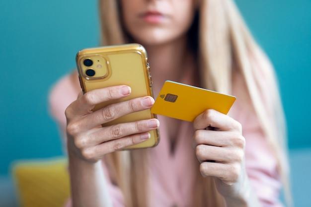 Nahaufnahme einer ernsthaften jungen frau, die etwas online mit ihrer kreditkarte und dem smartphone bezahlt, während sie zu hause auf dem sofa sitzt.