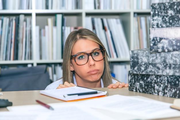 Nahaufnahme einer erschöpften blonden sekretärin, die mit viel arbeit auf ihrem desktop aussieht