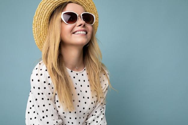 Nahaufnahme einer faszinierend lächelnden positiven jungen blonden frau mit sommerkleid strohhut und stilvoller sonnenbrille einzeln auf blauer hintergrundwand mit blick auf die seite