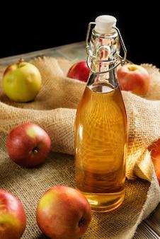 Nahaufnahme einer flasche hausgemachten apfelwein. flasche apfelsaft mit äpfeln auf einem sackleinenhintergrund.