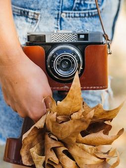 Nahaufnahme einer fotokamera, die von einer frau gehalten wird