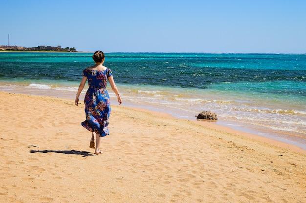 Nahaufnahme einer frau, die an einem sonnigen tag am strand spazieren geht