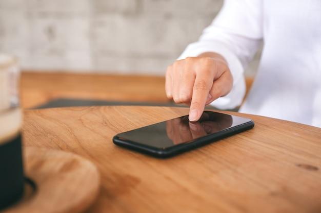 Nahaufnahme einer frau, die auf einem holztisch auf den bildschirm eines mobiltelefons zeigt und ihn berührt