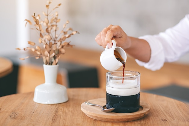 Nahaufnahme einer frau, die auf einem holztisch im café kaffee in ein glas eis und milch gießt
