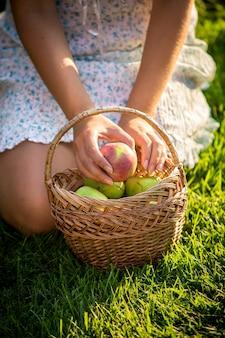 Nahaufnahme einer frau, die auf gras mit einem korb voller grüner äpfel sitzt