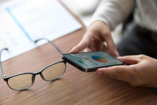 Nahaufnahme einer frau, die auf ihrem smartphone mit brille und finanzbericht auf finanzdiagramm schaut?