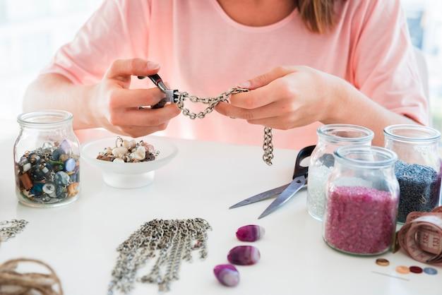 Nahaufnahme einer frau, die das handgemachte armband mit kette und perlen macht