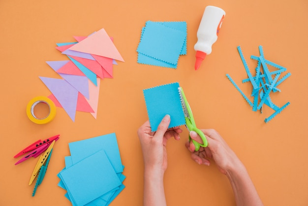 Nahaufnahme einer frau, die das papier mit scissor auf farbigem hintergrund schneidet