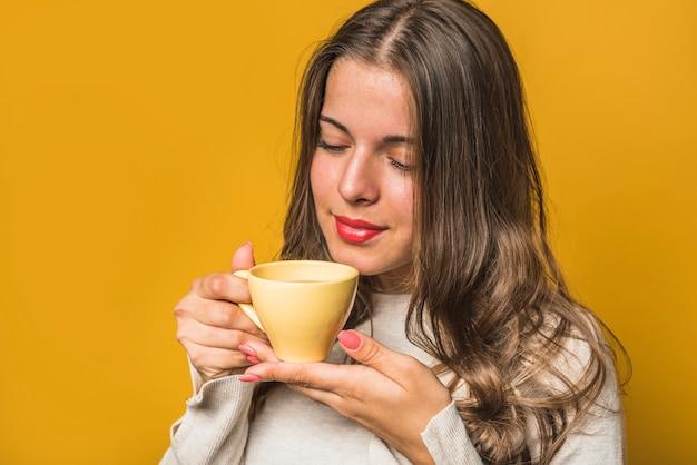 Nahaufnahme einer frau, die den kaffee von der gelben schale riecht