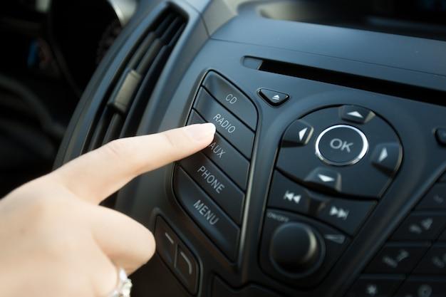Nahaufnahme einer frau, die den radioknopf auf dem armaturenbrett des autos drückt pressing