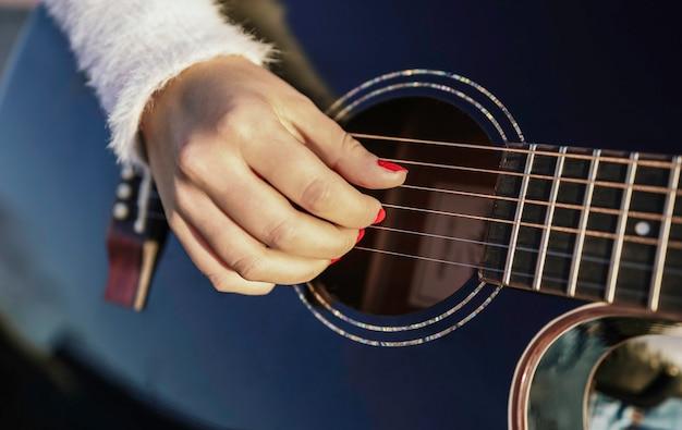Nahaufnahme einer frau, die die gitarre spielt