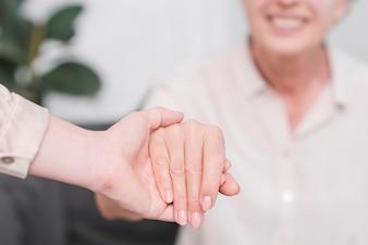 Nahaufnahme einer Frau, die die Hand der älteren Frau hält