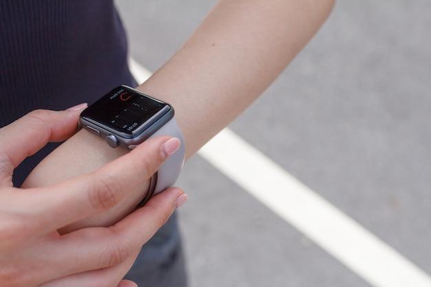 Nahaufnahme einer frau, die die herzfrequenz auf der smartwatch betrachtet.