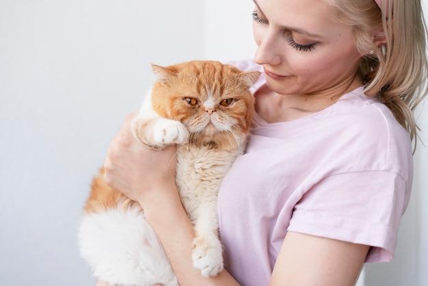 Nahaufnahme einer frau, die eine entzückende katze hält
