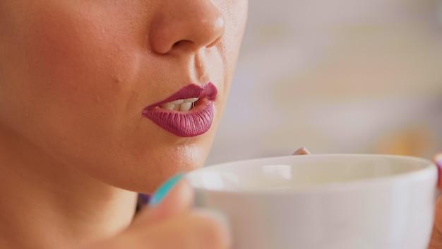 Nahaufnahme einer frau, die eine tasse heißen grünen tee hält und versucht, ihn zu trinken. hübsche dame, die morgens während des frühstücks in der küche sitzt und sich mit leckerem natürlichem kräutertee aus weißer teetasse entspannt.