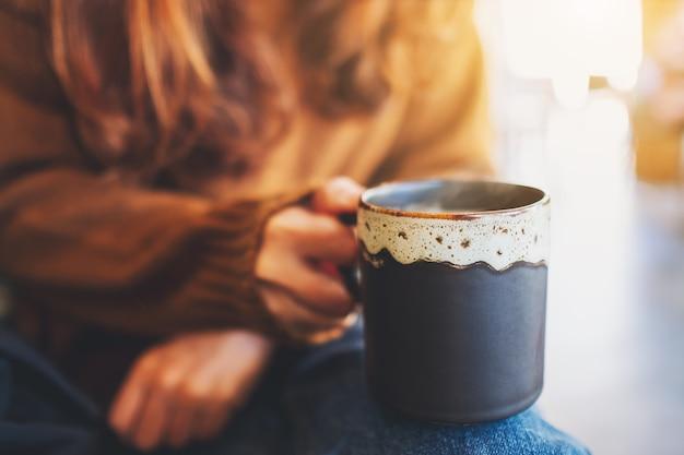 Nahaufnahme einer frau, die eine tasse heißen kaffee hält