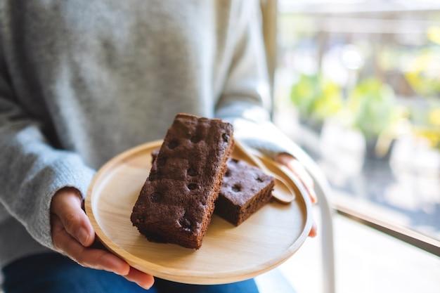 Nahaufnahme einer frau, die einen brownie-kuchen in einer holzplatte hält