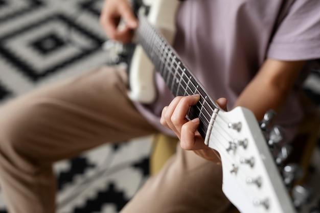 Nahaufnahme einer frau, die gitarre spielt