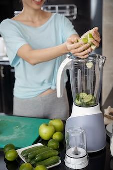 Nahaufnahme einer frau, die grünes obst und gemüse in den mixer legt, während sie smoothie macht