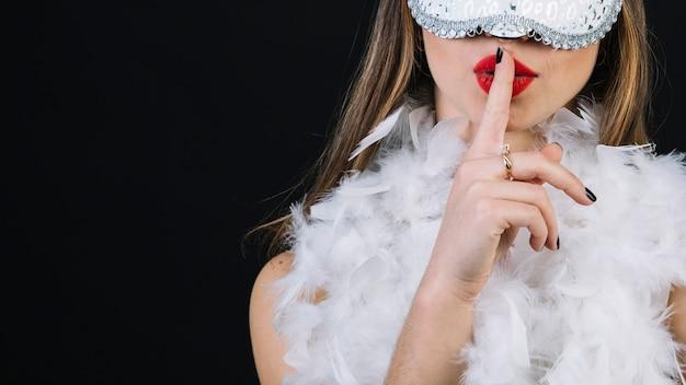 Nahaufnahme einer frau, die karnevalsmaske mit dem finger auf ihren lippen trägt