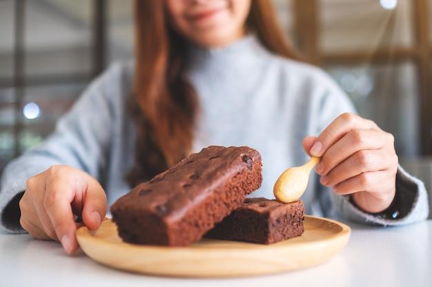 Nahaufnahme einer frau, die köstlichen brownie-kuchen mit löffel isst