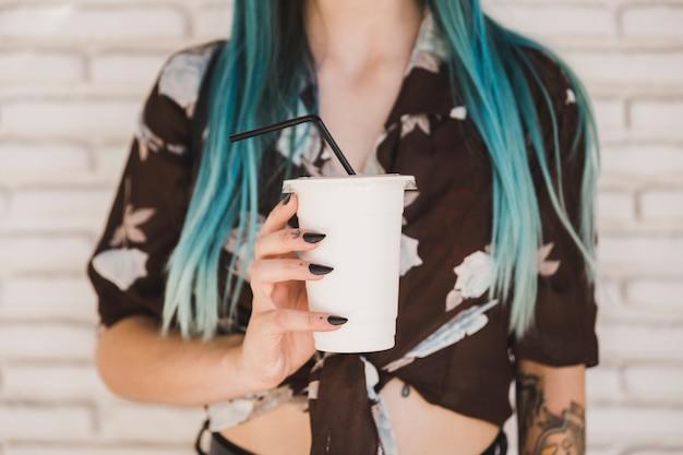 Nahaufnahme einer frau, die mitnehmerkaffeetasse hält