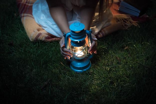 Nahaufnahme einer frau, die nachts auf gras sitzt und händchen an der laterne hält
