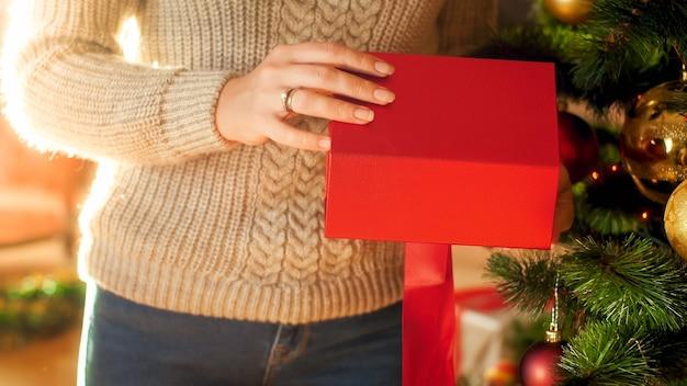 Nahaufnahme einer frau, die neben dem weihnachtsbaum steht und eine rote geschenkbox öffnet