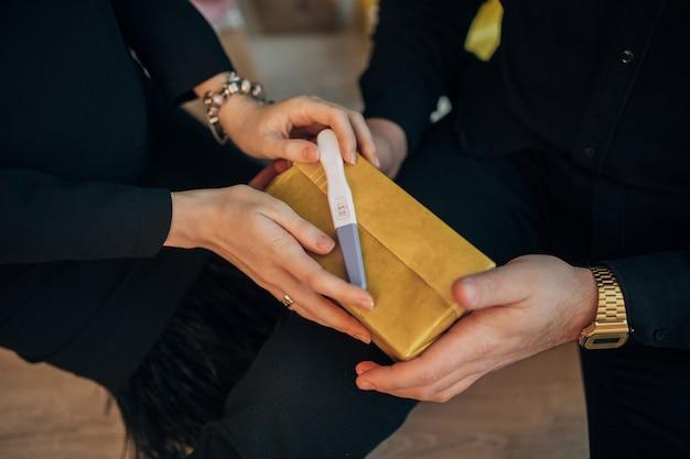 Nahaufnahme einer frau, die positiven schwangerschaftstest hält und darauf wartet, ihren geliebten zu überraschen