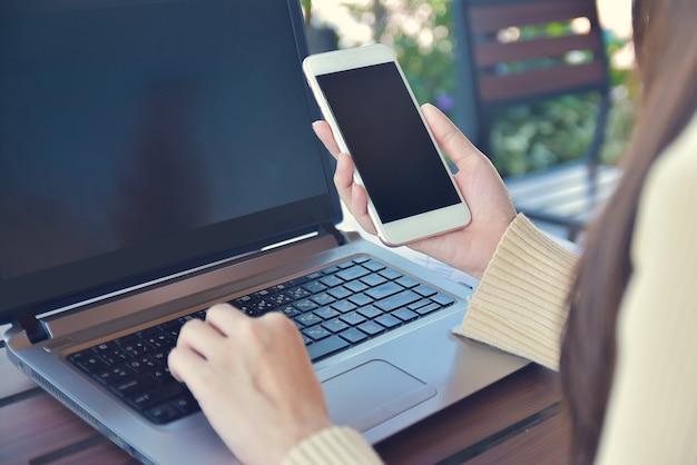 Nahaufnahme einer frau, die smartphone-mock-up-kopierspezifikation auf dem bildschirm hält