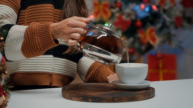 Nahaufnahme einer frau, die tee aus dem wasserkocher in die tasse gießt?