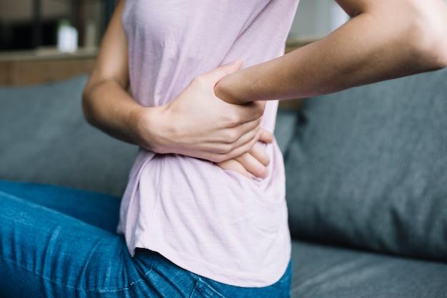 Nahaufnahme einer frau, die unter rückenschmerzen leidet