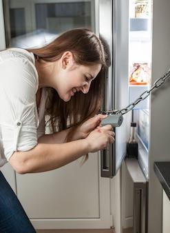 Nahaufnahme einer frau, die versucht, das am kühlschrank hängende schloss zu öffnen open