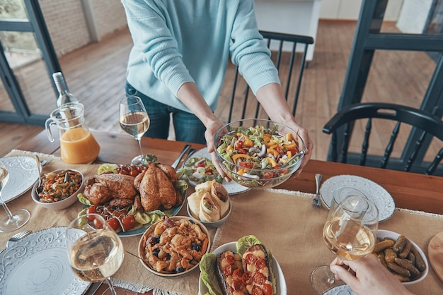Nahaufnahme einer frau, die während des familientreffens essen auf dem tisch serviert?