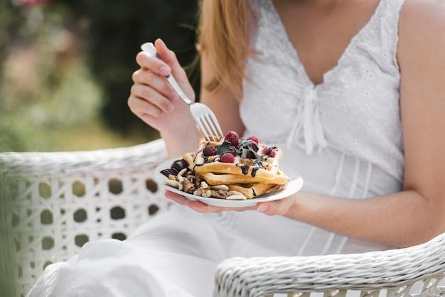 Nahaufnahme einer frau, die waffel auf frühstück isst