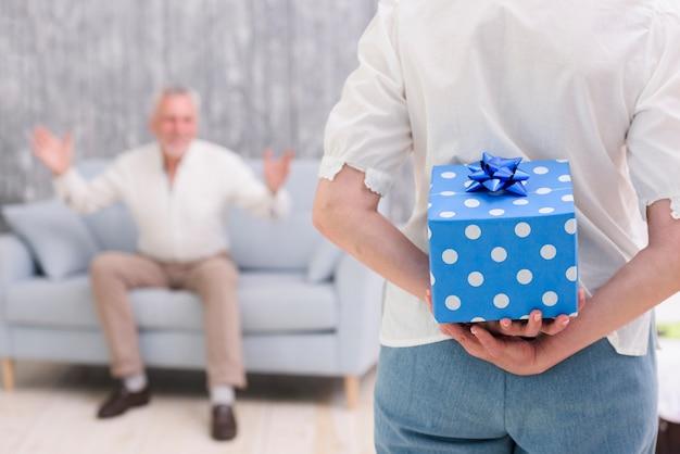 Nahaufnahme einer frau, die zurück geschenkbox hinter ihr versteckt, überraschend ihren ehemann