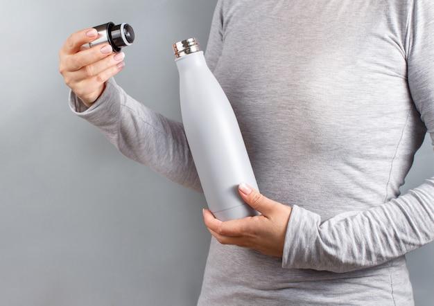 Nahaufnahme einer frau im grauen t-shirt mit grauer isolierflasche auf grauem hintergrund