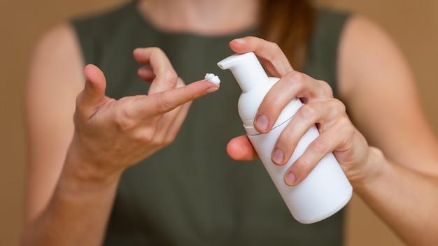 Nahaufnahme einer frau im grünen kleid unter verwendung der handfeuchtigkeitscreme.