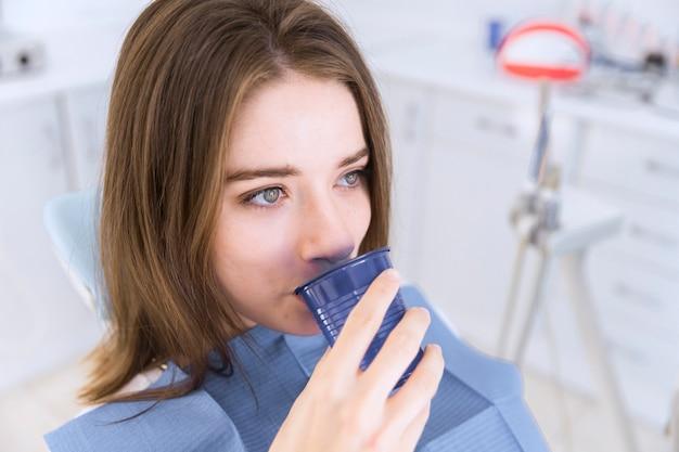 Nahaufnahme einer frau im zahnmedizinischen stuhl nehmen glas wasser
