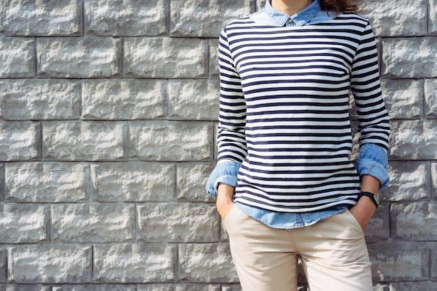 Nahaufnahme einer frau in einem jeanshemd, gestreiftem t-shirt und beige hosen mit einem fitness-tracker zur hand auf ziegelmauer im freien