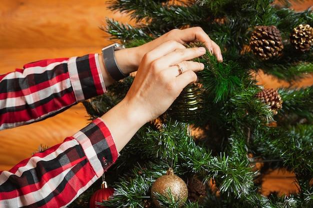 Nahaufnahme einer frau in einem karierten hemd hängt eine schöne glänzende kugel an einem weihnachtsbaum