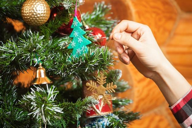 Nahaufnahme einer frau in einem karierten hemd hängt einen schönen glänzenden stern an einem weihnachtsbaum