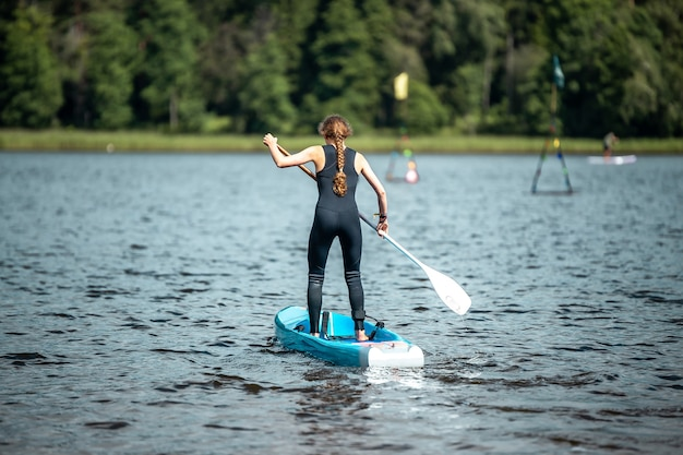 Nahaufnahme einer frau in einem schwarzen sportanzug, die auf einem see im sup-wettbewerb paddelt