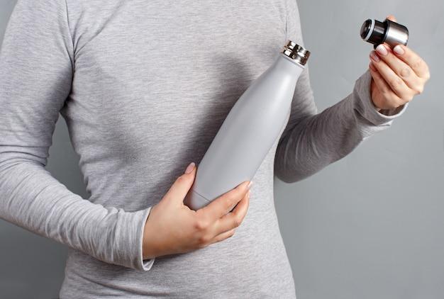 Nahaufnahme einer frau in grauem t-stück, die graue isolierflasche auf gelbem hintergrund öffnet