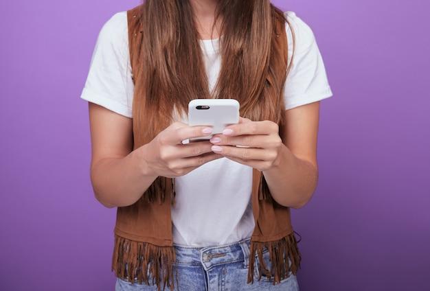 Nahaufnahme einer frau mit dem dunklen haar, das ein telefon in ihren händen hält.
