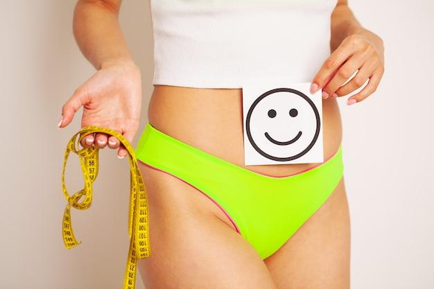 Nahaufnahme einer frau mit einer schlanken figur zeigt das ergebnis, das eine karte nahe ihrem bauch mit einem lächelnden lächeln und gelbem maßband hält.